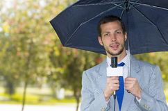 Successful handsome male journalist wearing light. Successful handsome male journalist in light grey suit working in rainy weather outdoors in park environment Stock Photo