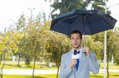 Successful handsome male journalist wearing light. Successful handsome male journalist in light grey suit working in rainy weather outdoors in park environment Stock Photos