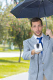 Successful handsome male journalist wearing light. Successful handsome male journalist in light grey suit working in rainy weather outdoors in park environment Stock Photography