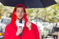 Successful handsome male journalist wearing red. Successful handsome male journalist in red rain jacket working in rainy weather outdoors in park environment Royalty Free Stock Image