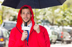 Successful handsome male journalist wearing red. Successful handsome male journalist in red rain jacket working in rainy weather outdoors in park environment Royalty Free Stock Photography