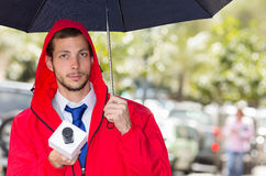 Successful handsome male journalist wearing red. Successful handsome male journalist in red rain jacket working in rainy weather outdoors in park environment Stock Images