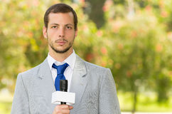 Successful handsome male news reporter wearing. Successful handsome male news reporter in light grey suit working outdoors in park environment holding microphone Stock Photos