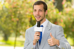 Successful handsome male news reporter wearing. Successful handsome male news reporter in light grey suit working outdoors in park environment holding microphone Royalty Free Stock Photo