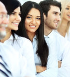 Successful and happy business team on office background. Girl looks out from the crowd in the frame Royalty Free Stock Photography