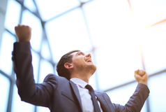 Successful happy businessman raises his arms up celebrating his victory Stock Photo