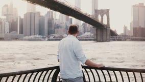 Successful happy businessman stands near Brooklyn Bridge embankment fence panorama in New York City, back view 4K. Successful happy businessman stands near stock footage
