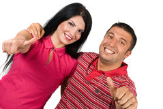Successful happy couple with thumbs-up. Young happy couple embrace giving thumbs-up and man holding his hand on woman shoulders and both smiling for camera ,left Royalty Free Stock Images