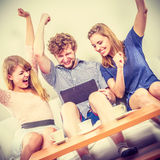 Successful happy friends with tablet. Stock Photo