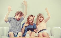 Successful happy friends with tablet at home. Successful happy friends with hands up browsing surfing internet on tablet. Young people men guy and women girls Royalty Free Stock Photography