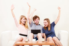Successful happy friends with tablet at home. Stock Photo
