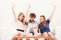 Successful happy friends with tablet at home. Stock Photos