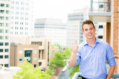 Successful, happy, handsome guy giving thumbs up on his balcony Stock Photo