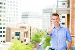 Successful, happy, handsome guy giving thumbs up on his balcony Stock Image