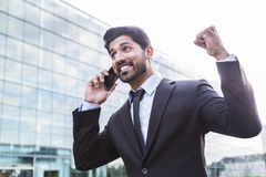 Successful businessman or worker in suit with phone near office building. Successful happy smiling arabic eastern indian businessman or worker in black suit with royalty free stock photos