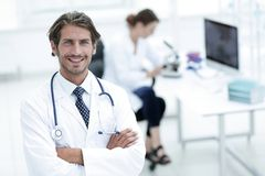 Handsome male doctor smiling with arms crossed on chest portrait. Successful happy smiling male doctor with phonendoscope Royalty Free Stock Photos