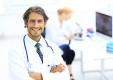 Handsome male doctor smiling with arms crossed on chest portrait. Successful happy smiling male doctor with phonendoscope Stock Image