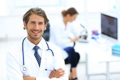 Handsome male doctor smiling with arms crossed on chest portrait. Successful happy smiling male doctor with phonendoscope Royalty Free Stock Image