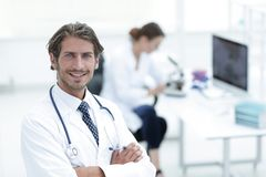 Handsome male doctor smiling with arms crossed on chest portrait. Successful happy smiling male doctor with phonendoscope Royalty Free Stock Photo