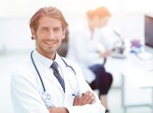 Handsome male doctor smiling with arms crossed on chest portrait. Successful happy smiling male doctor with phonendoscope Stock Photo