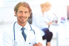 Handsome male doctor smiling with arms crossed on chest portrait. Successful happy smiling male doctor with phonendoscope Stock Photography