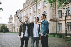 Successful happy students standing near campus or university outside. Three stylish students in a casual wear standing outside near the university and making Royalty Free Stock Images