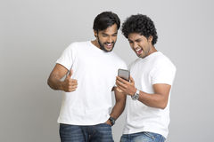 Successful happy two young men standing and using smartphone Royalty Free Stock Image