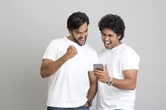 Successful happy two young men standing and using smartphone Royalty Free Stock Photo