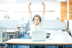 Successful happy young woman celebrating victory in office Stock Images