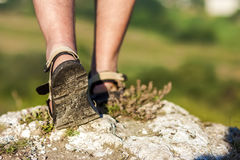 Successful hiker legs walking on mountain peak rock. Adventure a. Nd exercising in summer nature Stock Image
