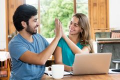 Successful hipster couple give high five. Indoor at home stock photo