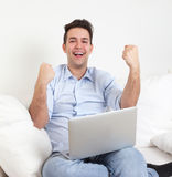 Successful hispanic guy with notebook on a sofa Royalty Free Stock Images