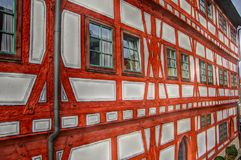 Large well-kept timbered house. Successful house renovation, Truss facade with row of Windows, great truss façade with red painted wooden beams, three-storey stock photos