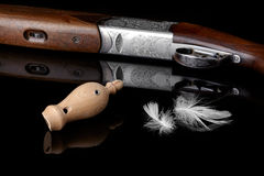 Successful hunt. Wooden whistles for calling ducks with a feather and a hunting gun Royalty Free Stock Photo