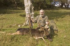 Successful hunter and prize. Successful hunter and fallow deer taken in New Zealand Stock Photography