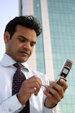 Successful Indian business man on phone. Successful Indian business man checking email on touch screen mobile phone Royalty Free Stock Images