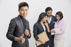 Successful Indian businessman with his busy colleagues Stock Photo