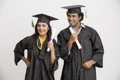 Successful Indian college graduates wearing cap and gown holding diploma Royalty Free Stock Photography