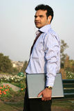 Successful indian techie. Young indian walking with laptop and mp3 player in the park Stock Image