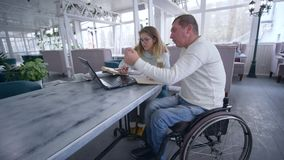 Successful invalid man restaurant owners on wheelchair with woman working on laptop computer for planning and managing stock video