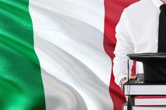 Successful Italian student education concept. Holding books and graduation cap over Italy flag background royalty free stock image