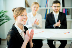 Successful job interview. A candidate is clasping her hands after her success Stock Image
