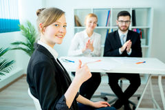Successful job interview. A candidate is showing thumbs up after her success Royalty Free Stock Photography