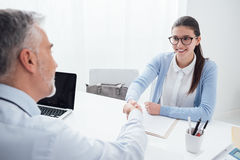 Successful job interview. Young smart women having a successful job interview, the examiner is shaking her hand royalty free stock images
