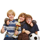 Successful kids with trophy. And soccer ball holding their thumbs up stock photo
