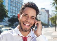 Successful latin businessman at phone in the city Royalty Free Stock Photos