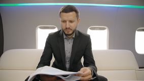 Successful lawyer businessman looking at documents sitting in first class of aircraft. entrepreneur plane stock video footage