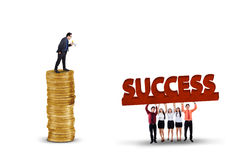 Successful leader give orders on employees. Successful businessman standing on the golden coins while giving orders his workers to lift a success text royalty free stock image