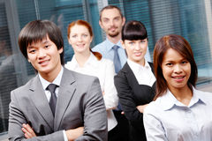 Successful leaders. Photo of successful business partners looking at camera with co-workers behind them royalty free stock photo