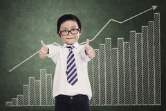 Successful little businessman over a business chart Stock Photos